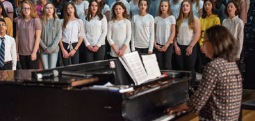 group of students singing while a woman plays the piano
